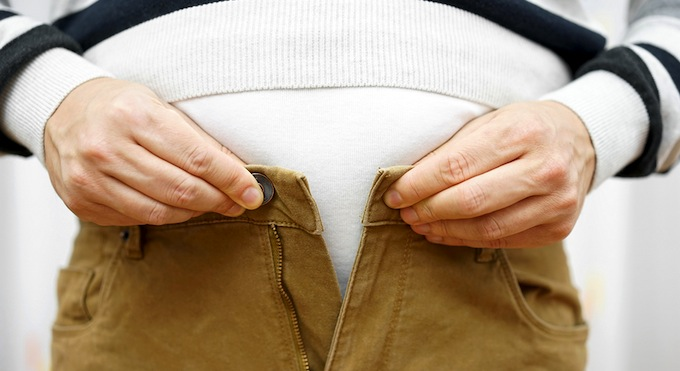 Man unable to do up his cord trousers due to weight gain.